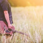 A man holding a guitar in a field.