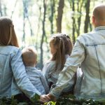 A family of four facing away from the camera looking into the forest of trees.